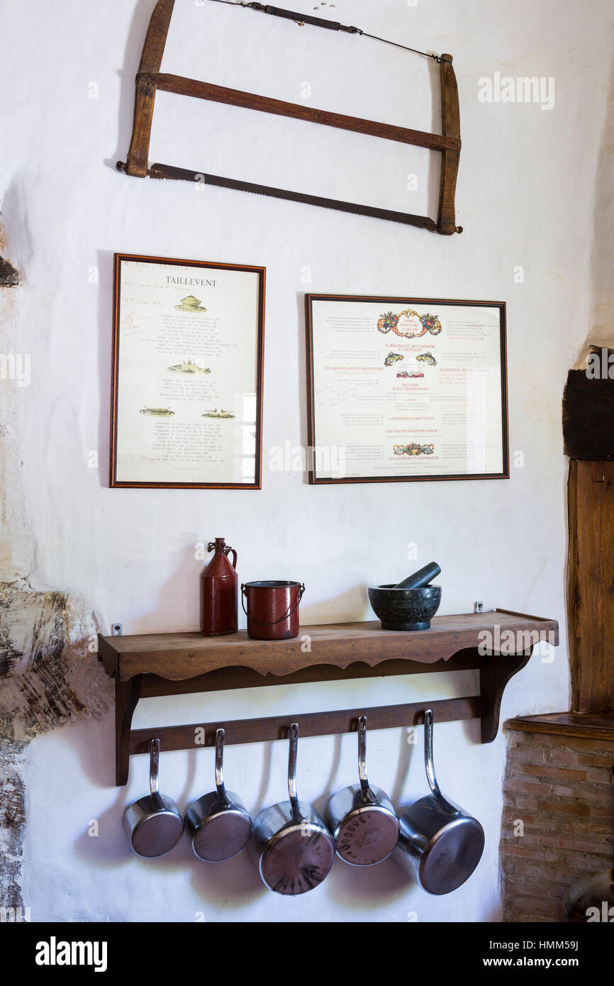 french country kitchen with hanging pans, wooden shelf and hand saw ...