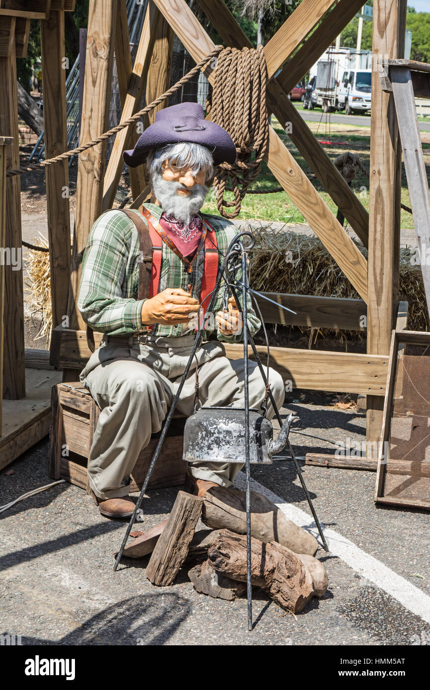 Model of an old Australian Prospector sitting in front of his cast iron kettle hanging over a camp fire. - Stock Image