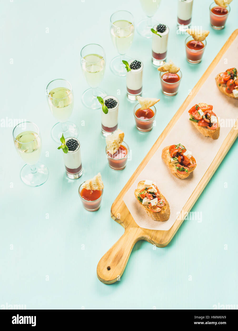 Snacks, brushettas, gazpacho shots, desserts, champagne over pastel blue background - Stock Image