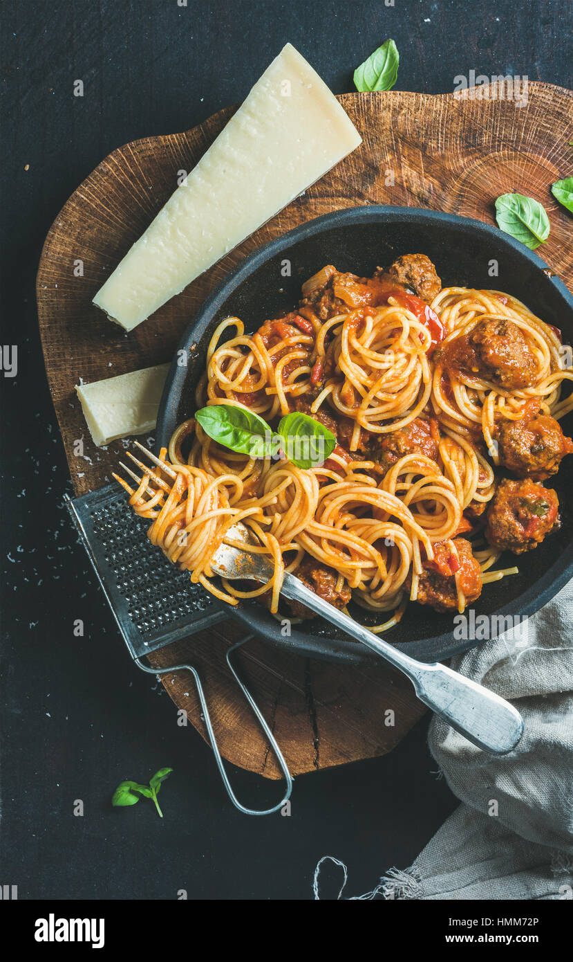 Spaghetti with meatballas, basil and parmesan cheese in black plate - Stock Image