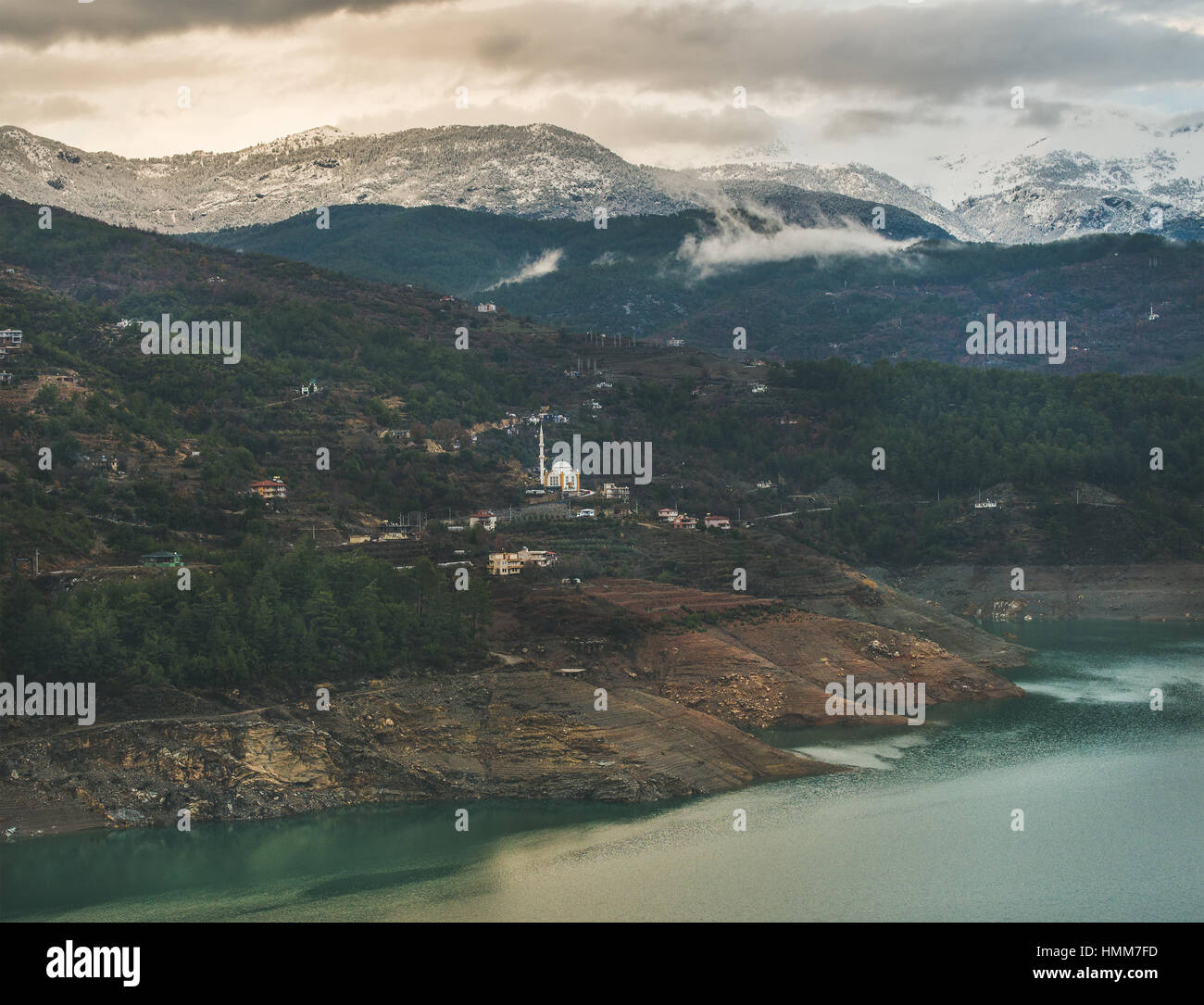 Dim Cay storage pond and mountains covered with snow, Alanya - Stock Image