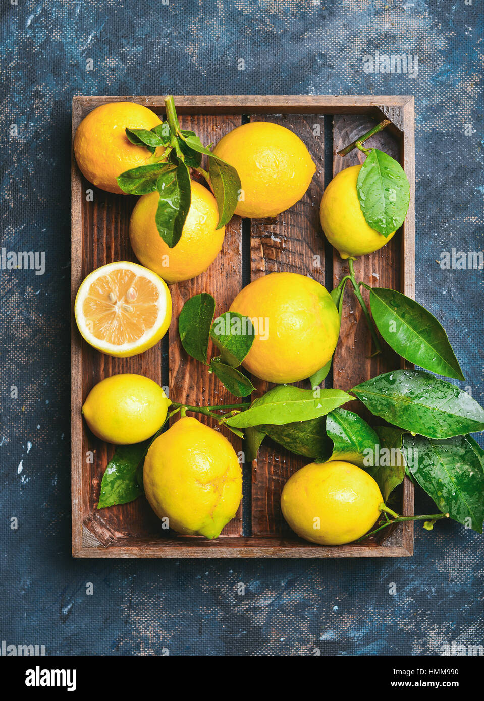 Freshly picked lemons with leaves in rustic wooden tray - Stock Image