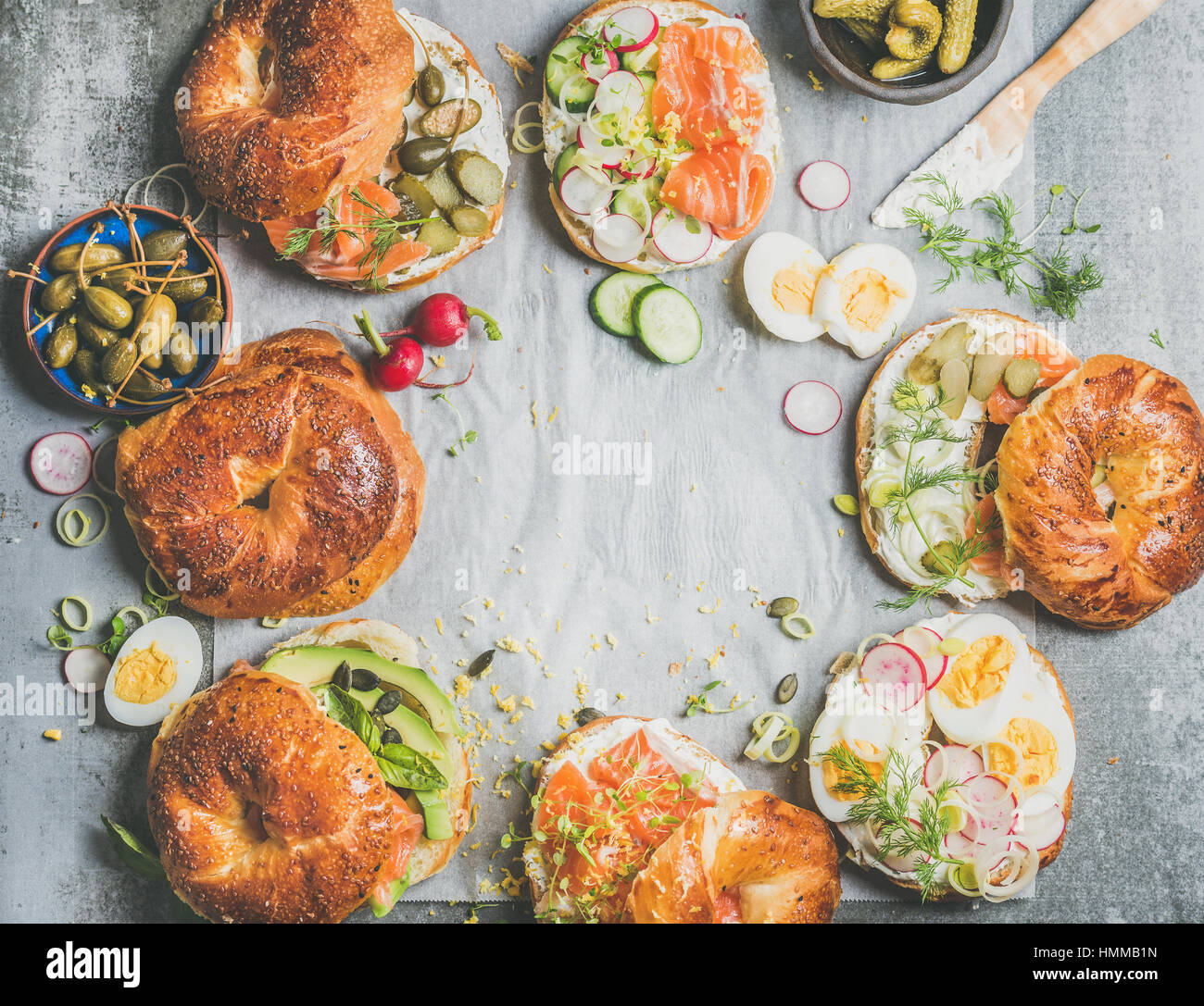 Variety of fresh bagels with different fillings, copy space - Stock Image