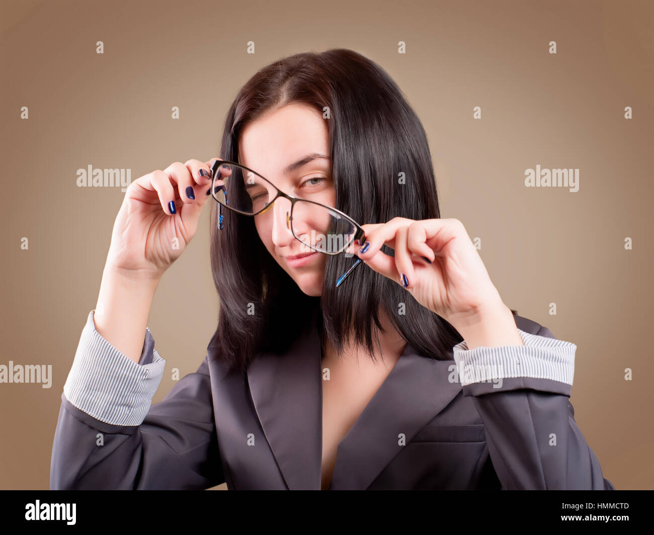 Malicious or tricky girl looking through the glasses. Studio shoot on brown background - Stock Image