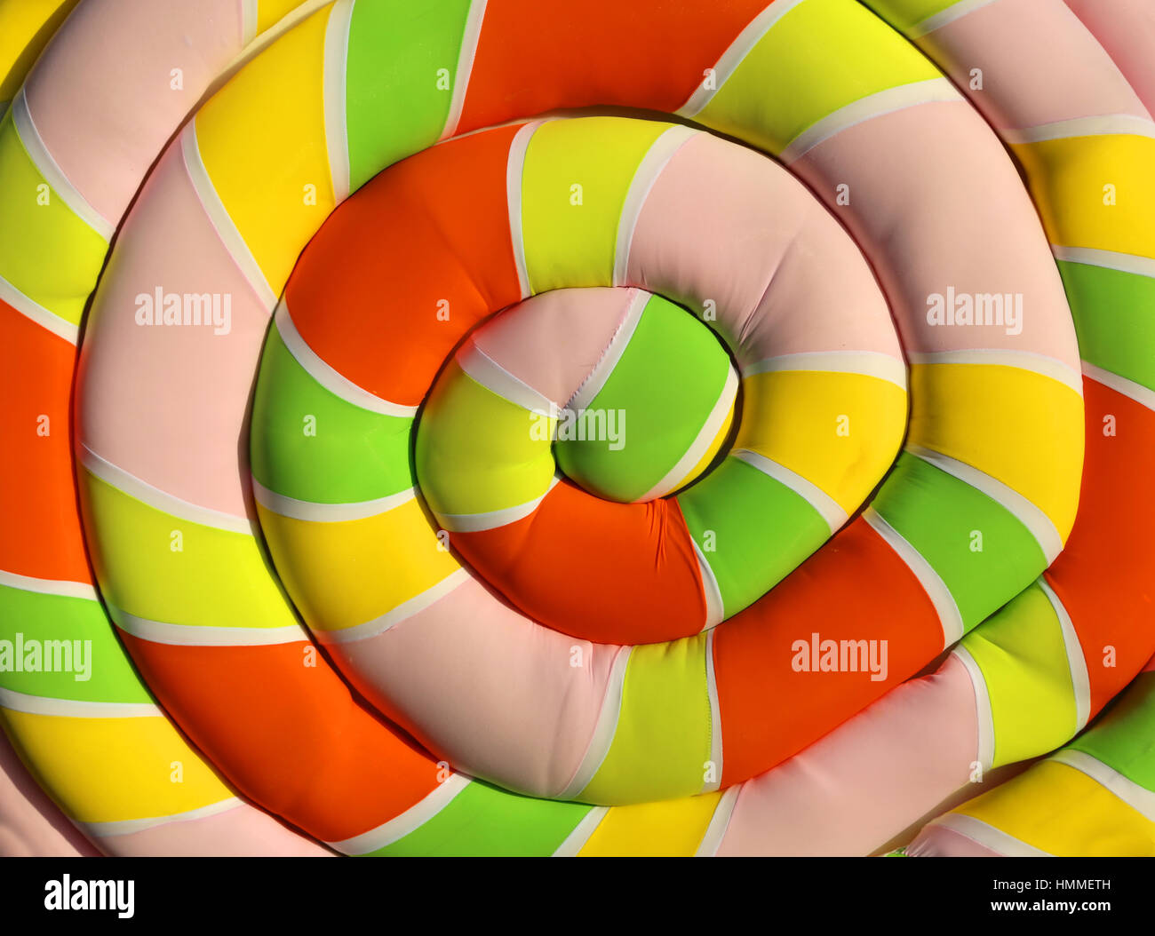 big soft pillow shaped like a giant marshmallow with a spiral colorful Stock Photo