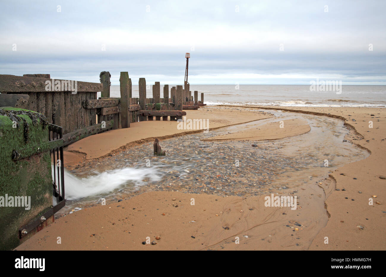 The outfall of the River Mun on the beach at Mundesley-on-Sea, Norfolk, England, United Kingdom. - Stock Image