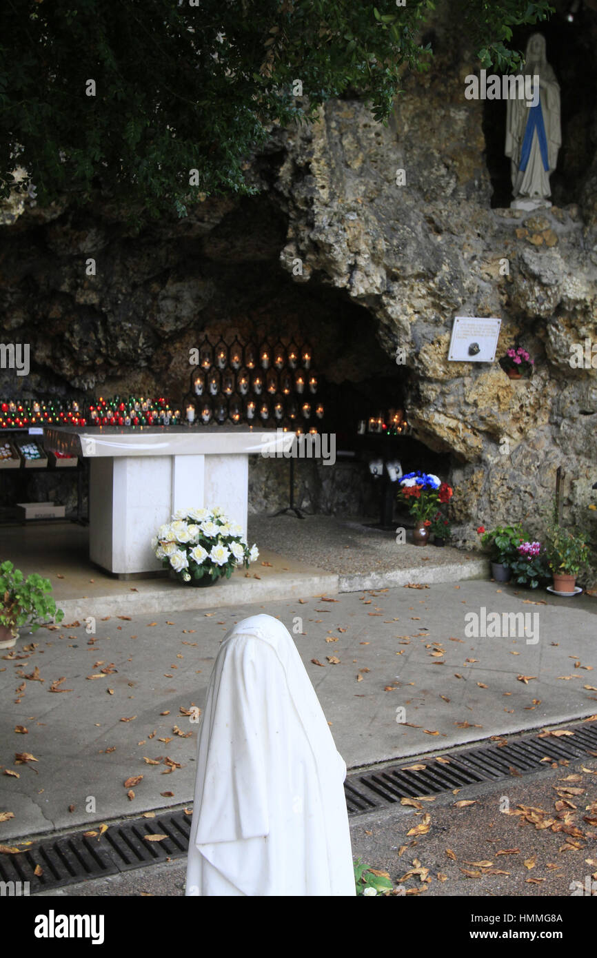 Sculpture de Bernadette Soubirous priant devant la statuette de la Vierge-Marie. Grotte de Lourdes. Couvent Saint Stock Photo