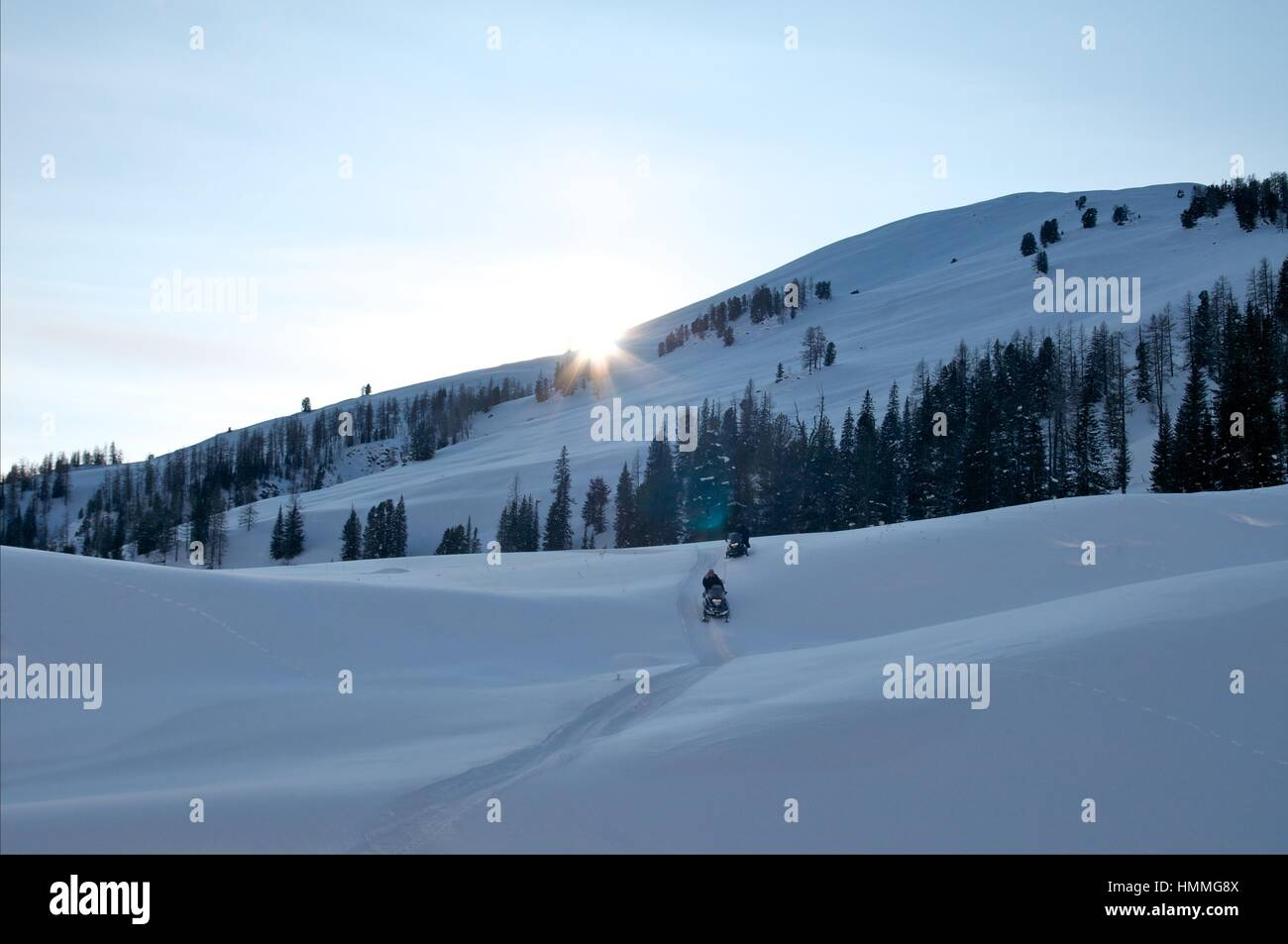 Two men on a snowmobile of mountains background - Stock Image