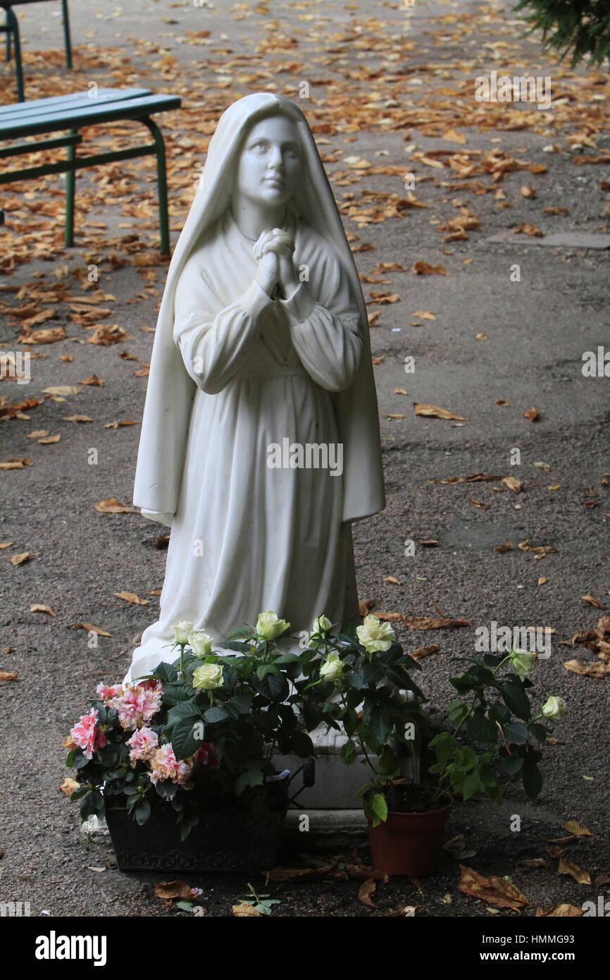 Sculpture de Bernadette Soubirous priant devant la statuette de la Vierge-Marie. Grotte de Lourdes. Couvent Saint - Stock Image