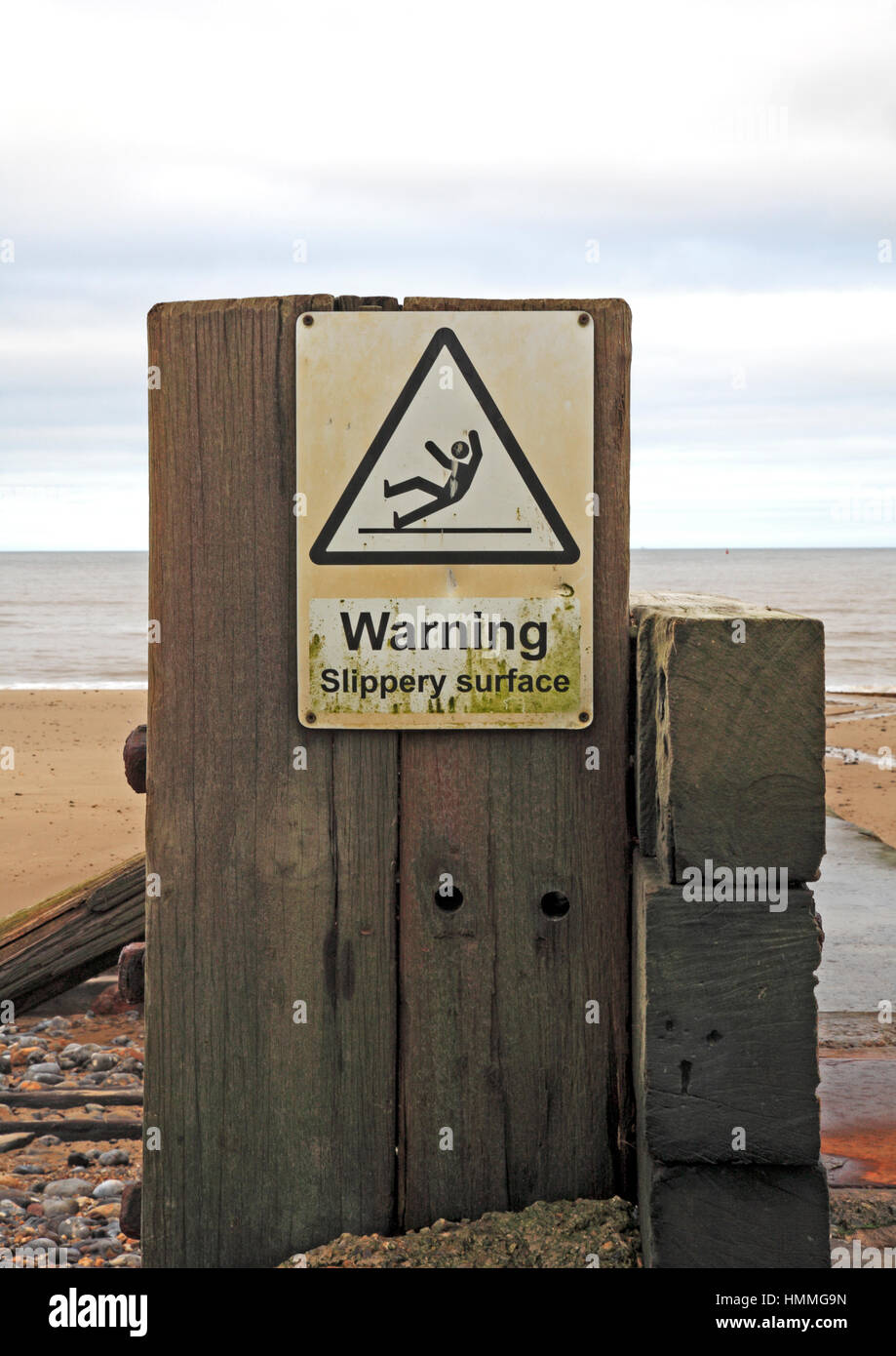 A slippery surface warning sign on the beach at Mundesley-on-Sea, Norfolk, England, United Kingdom. - Stock Image