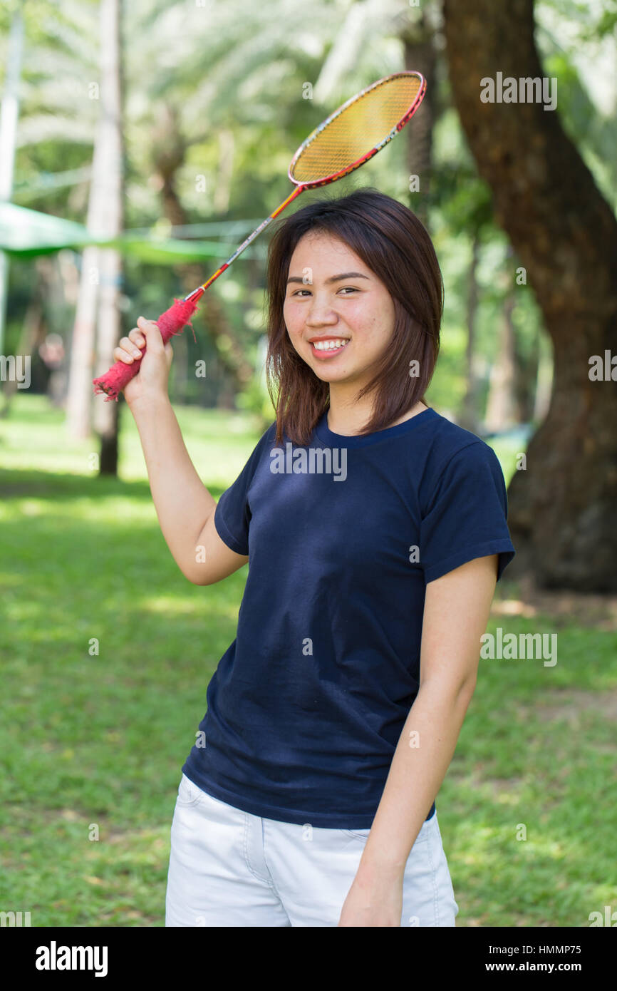 Asian teen relax play badminton in the park. - Stock Image