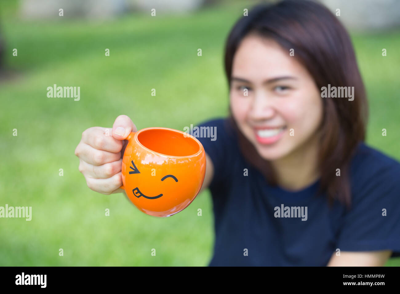 happy drink concept, Asian teen handle smile mug in the park. - Stock Image