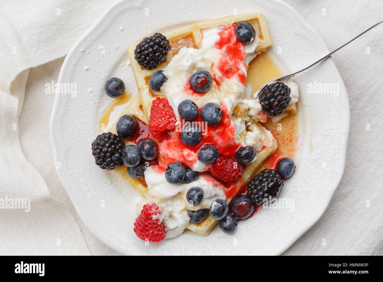 Waffles with raspberries, blueberries, whipped cream, berry fruit sauce and maple syrup - Stock Image