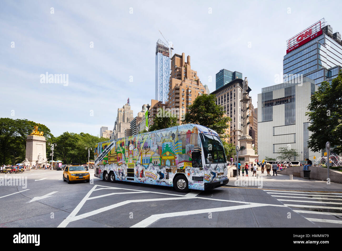 New York City - June 22: Painted bus at Columbus Circle in New York with blue sky and the new One57 tower in the Stock Photo
