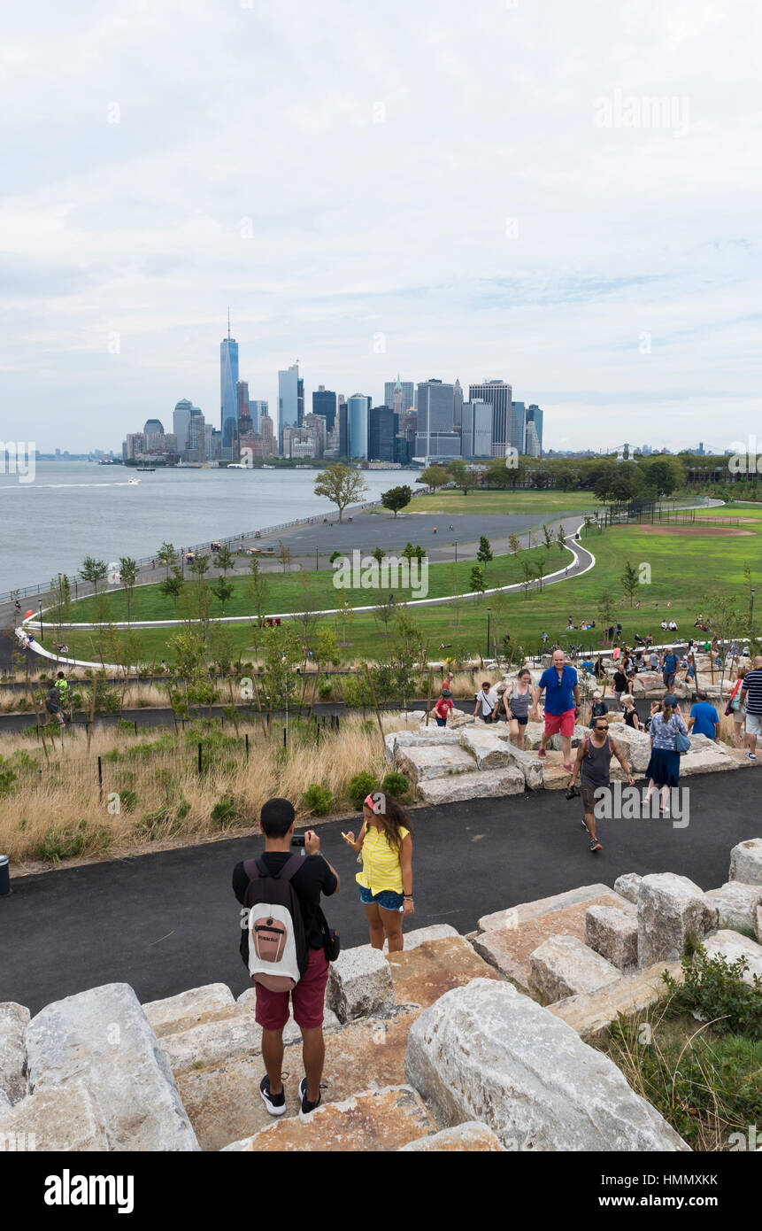 View from Outlook Hill over Grassy Hill, Governors Island, towards the skyline of New York City - Stock Image