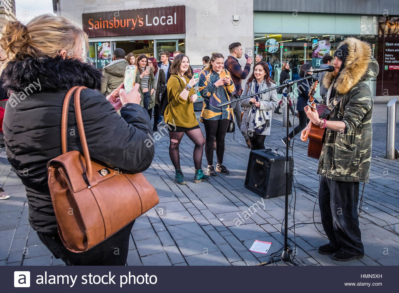 Bristol, UK - 04 February 2017:  Singer performs protest songs in front of young fans taking photos in the city - Stock Image