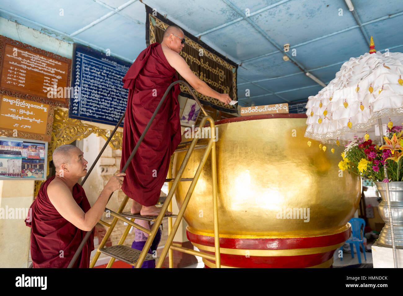 Myanmar (ex Birmanie). Bagan, Mandalay region. Temple of Manuha Paya. Monks depositing an offering in an immense - Stock Image