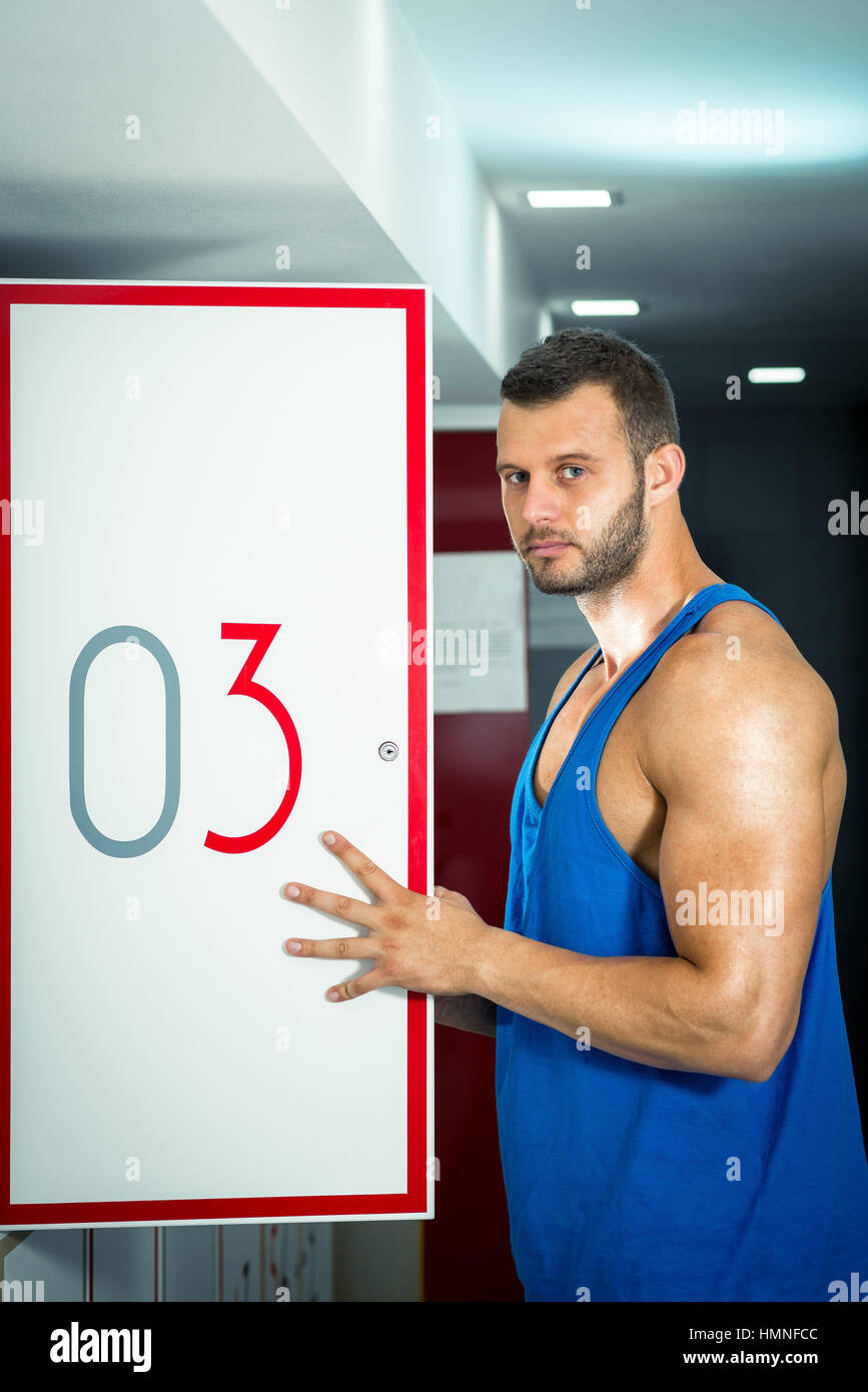 Young adult man opens locker door in