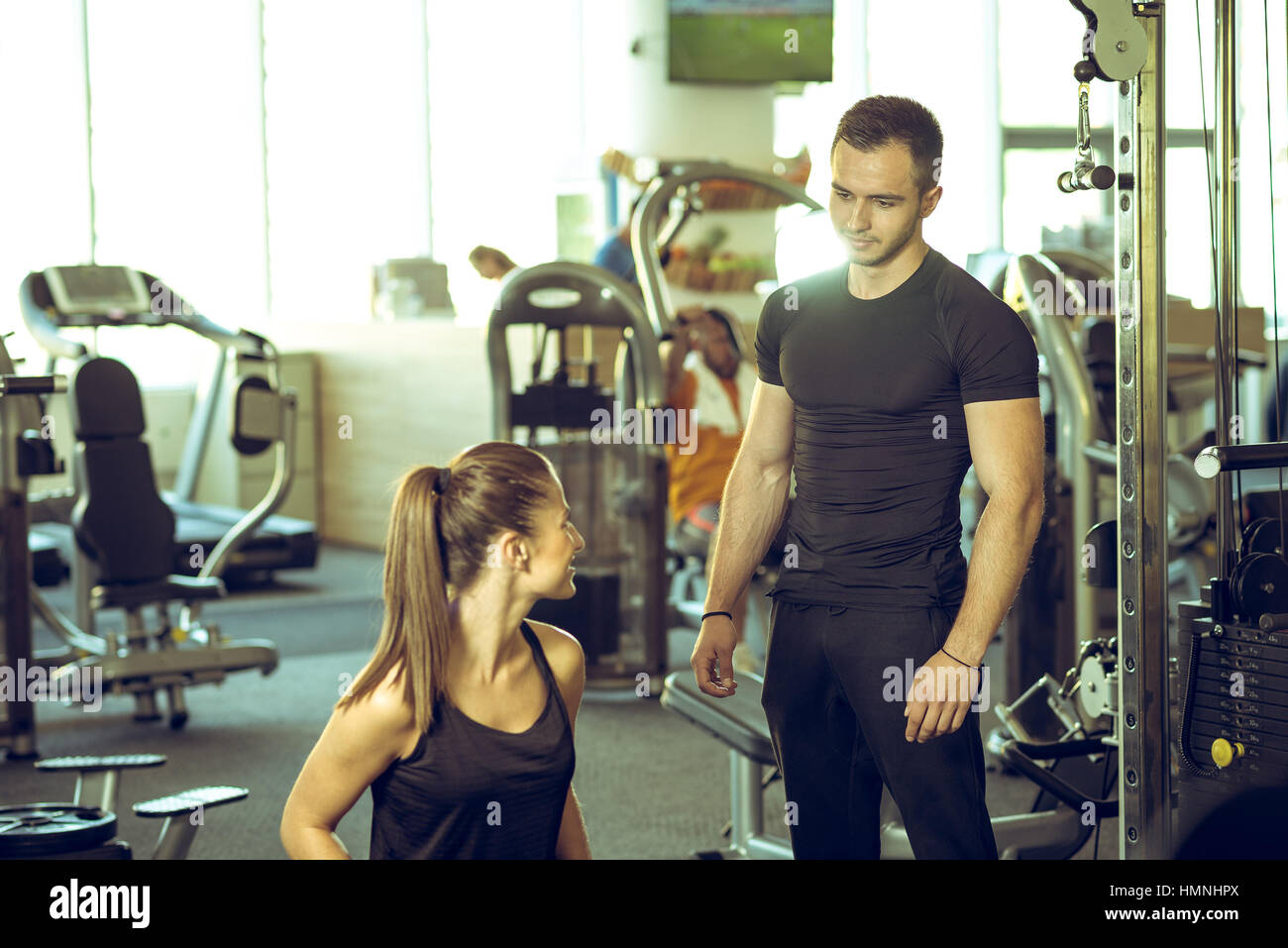 Young male personal fitness trainer talks to his female client and giving her advices for motivation. - Stock Image