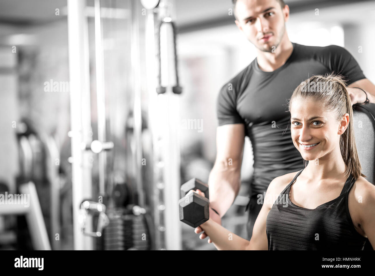 Young adult woman working out in gym, doing bicep curls with help of her personal trainer. - Stock Image