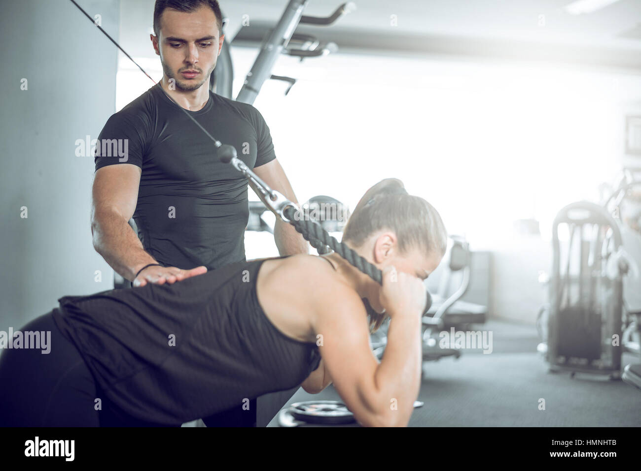 Young adult personal fitness trainer supporting his client while doing overhead rope extension. - Stock Image