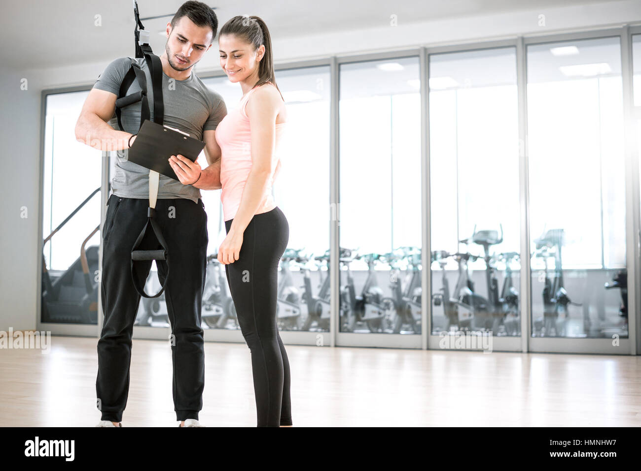 Personal trainer showing result of training plan to his female young client with suspension rope over shoulder. - Stock Image