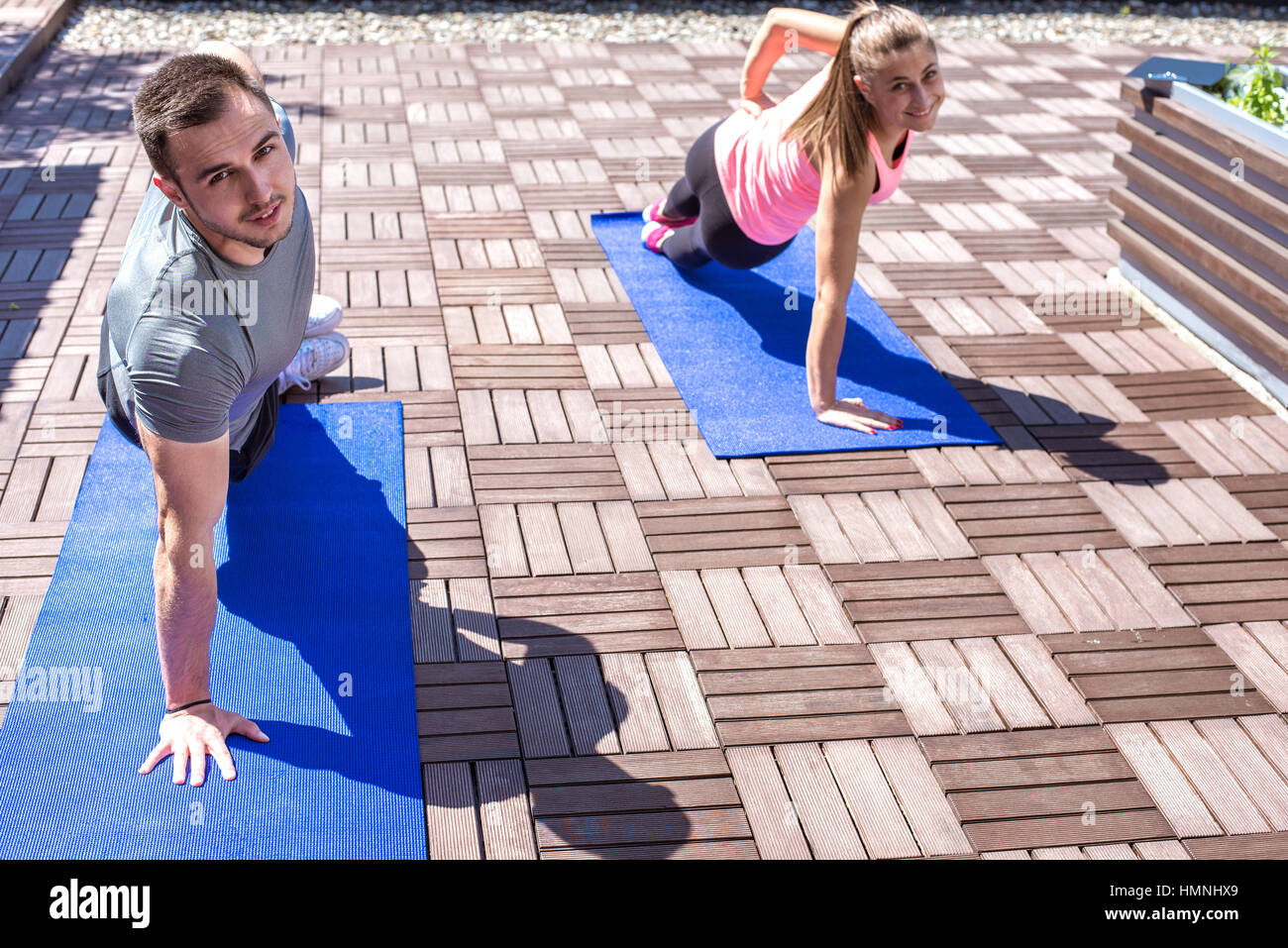 Young couple doing together side plank exercise on the rooftop, outdoors. Stock Photo