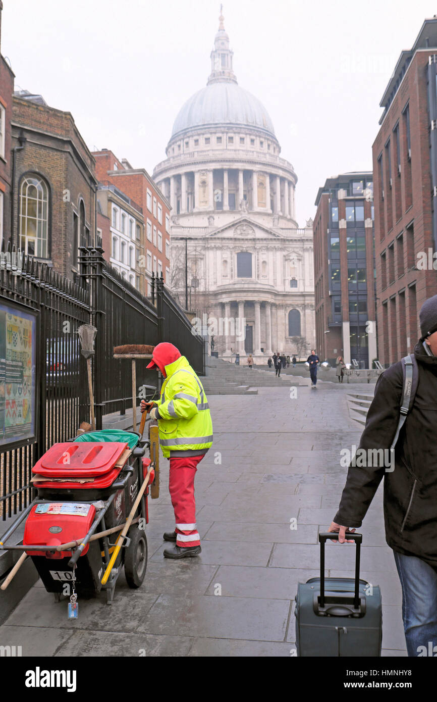 Street cleaner with dustcart in winter clothing working near St Pauls Cathedral in the City of London, UK   KATHY Stock Photo