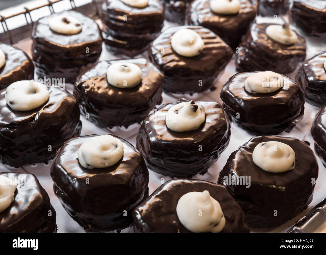 Delicious bakery display of cream filled chocolate frosted donuts - Stock Image