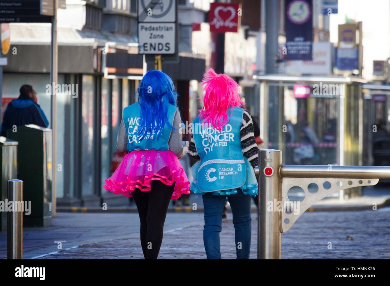 World cancer day canvassers, wearing coloured wigs, and colourful fluorescent skirton the streets collecting for Stock Photo