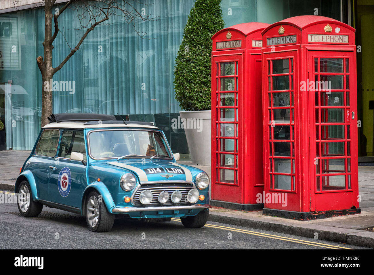 Austin Mini Cooper parked next to red telephone boxes in St Martin's Lane in central London - Stock Image