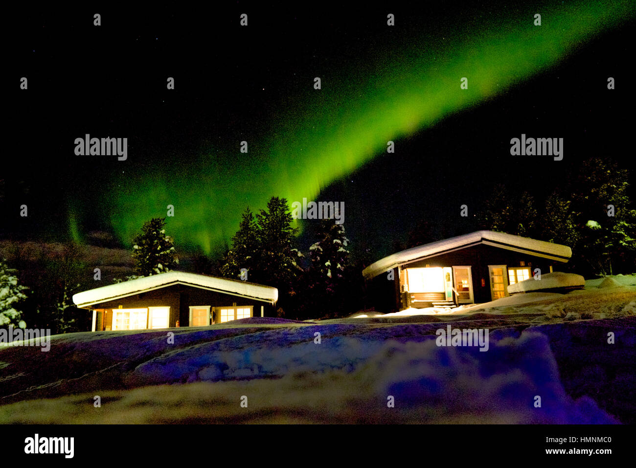 norther lights above snow covered cabins, night sky - Stock Image