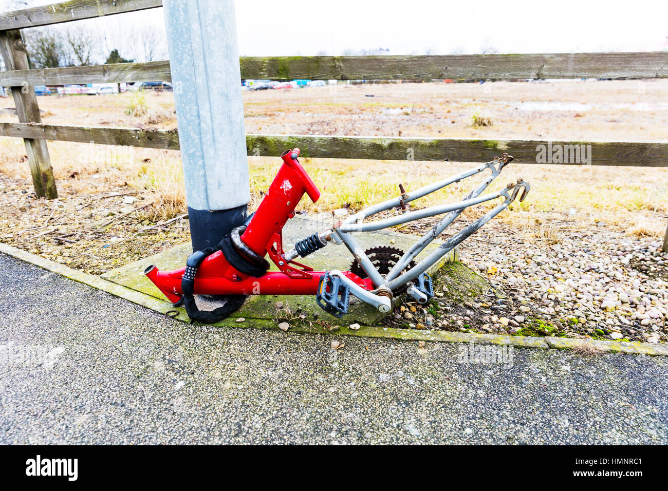 Secure bike pushbike secured to lamp post stripped bare of valuable parts wheels seat handlebars etc - Stock Image