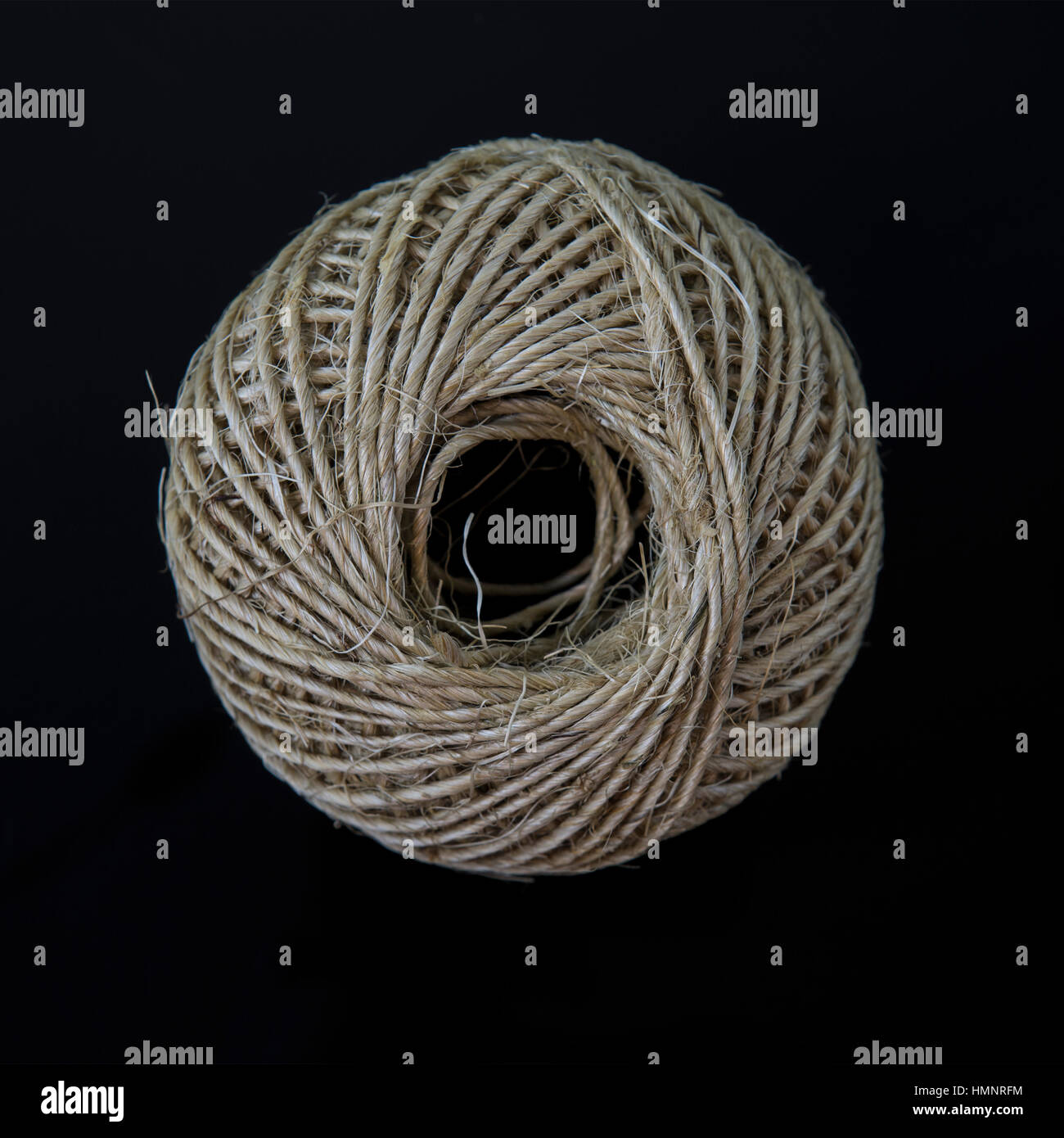 Ball of string on a black background - Stock Image