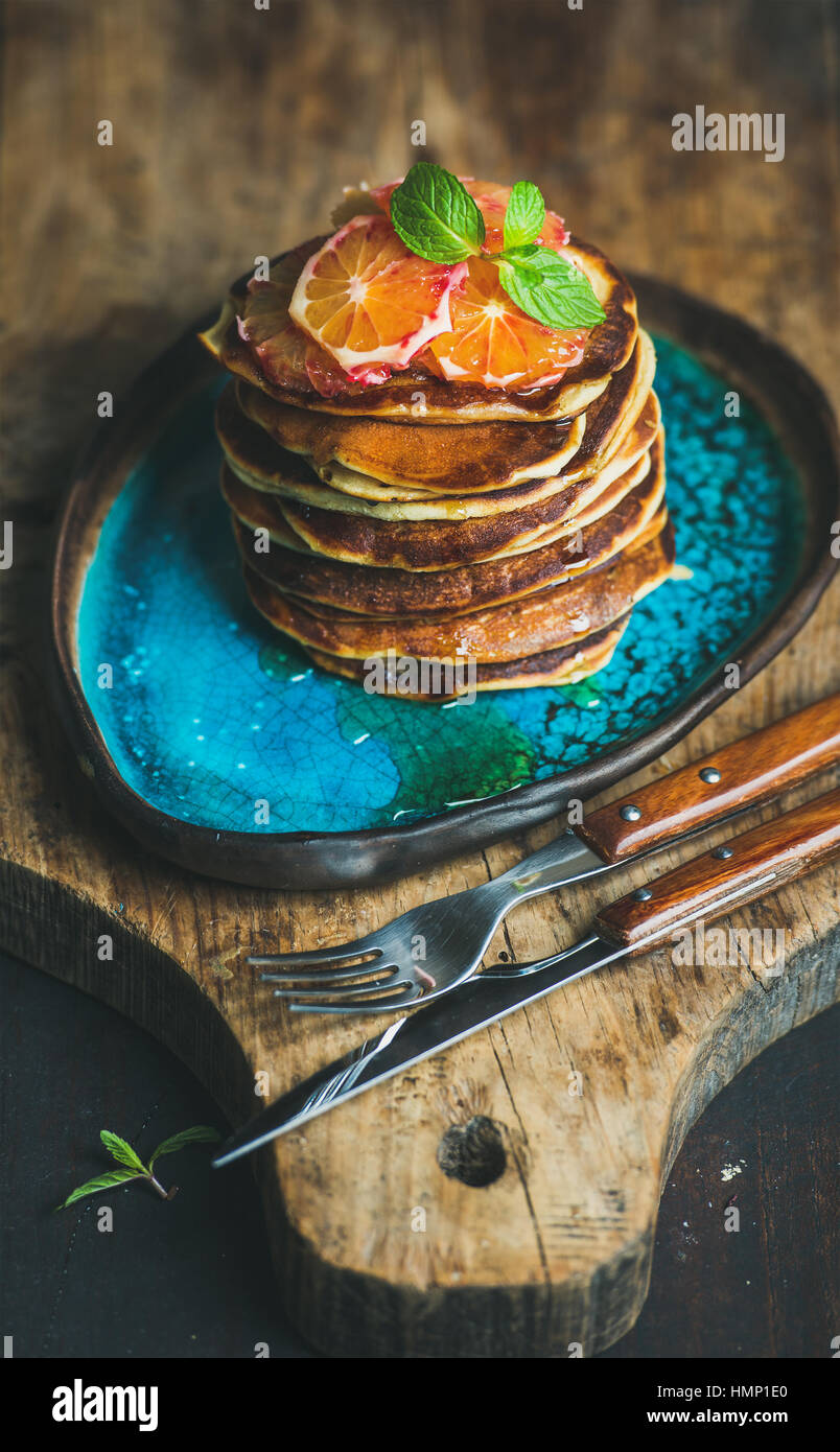 Homemade pancakes with honey, bloody orange slices and mint leaves - Stock Image