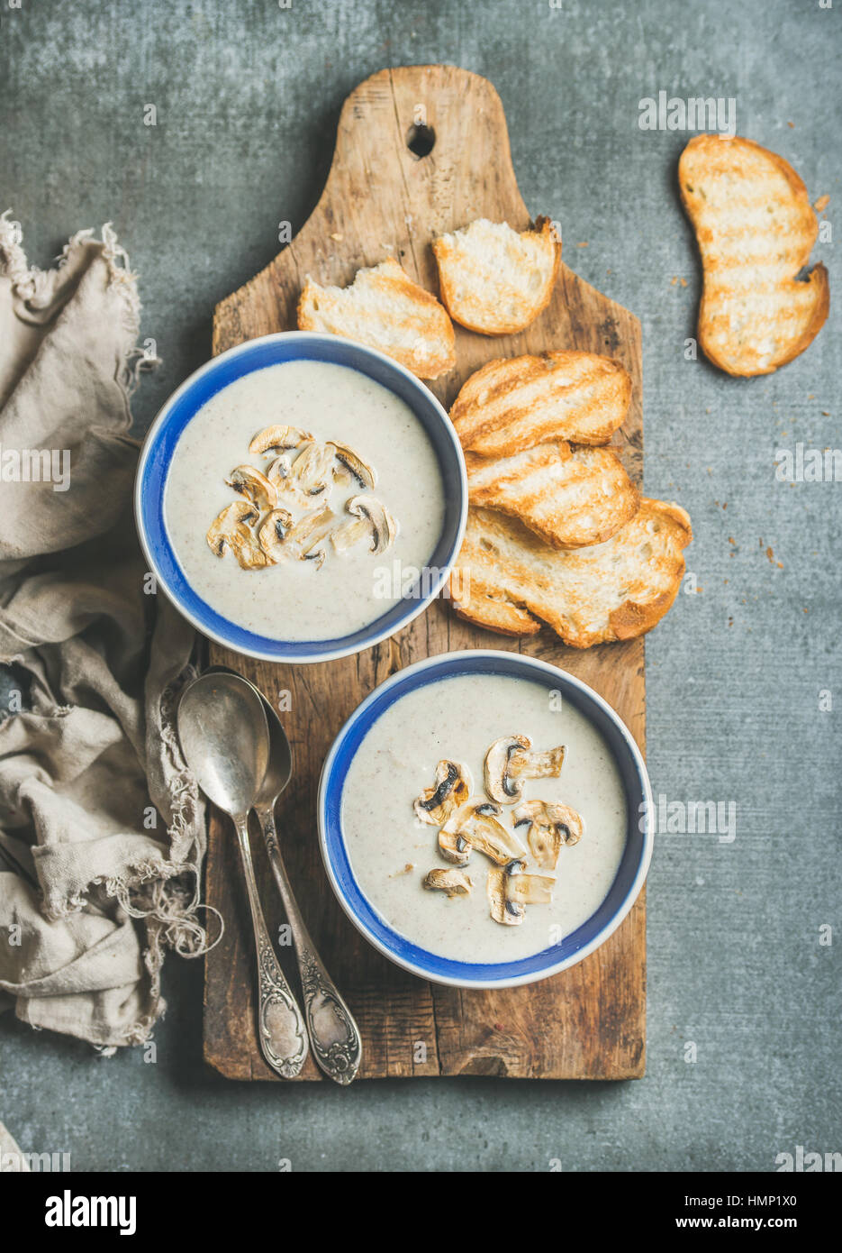 Creamy mushroom soup in bowls with toasted bread slices - Stock Image