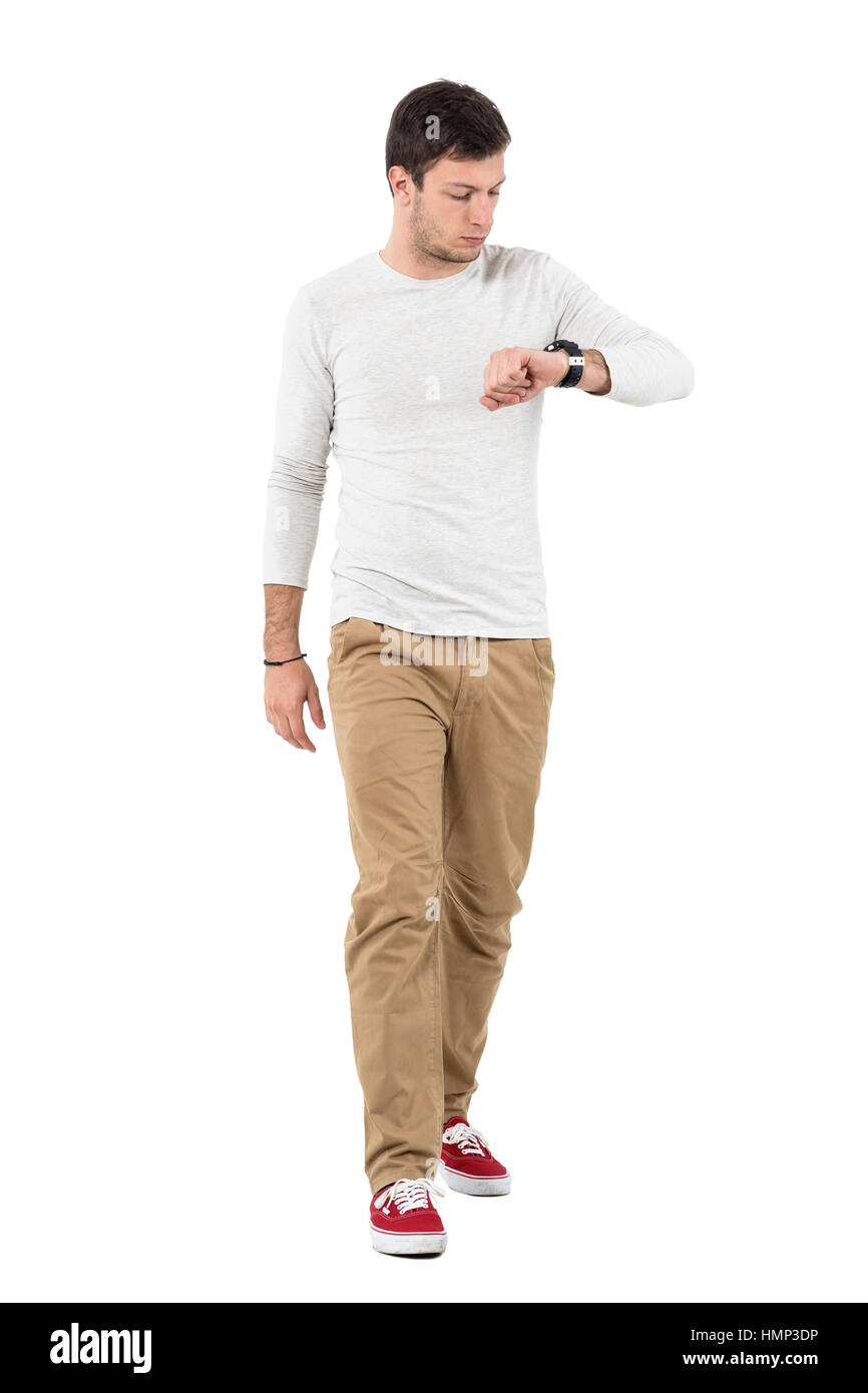 Stylish young man walking and checking time on wrist watch. Full body length portrait isolated over white studio - Stock Image