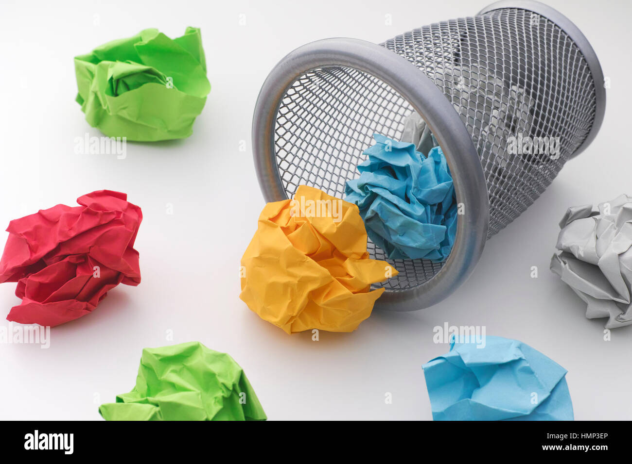 Colorful paper balls rolling out of trash can. Idea Concept. - Stock Image