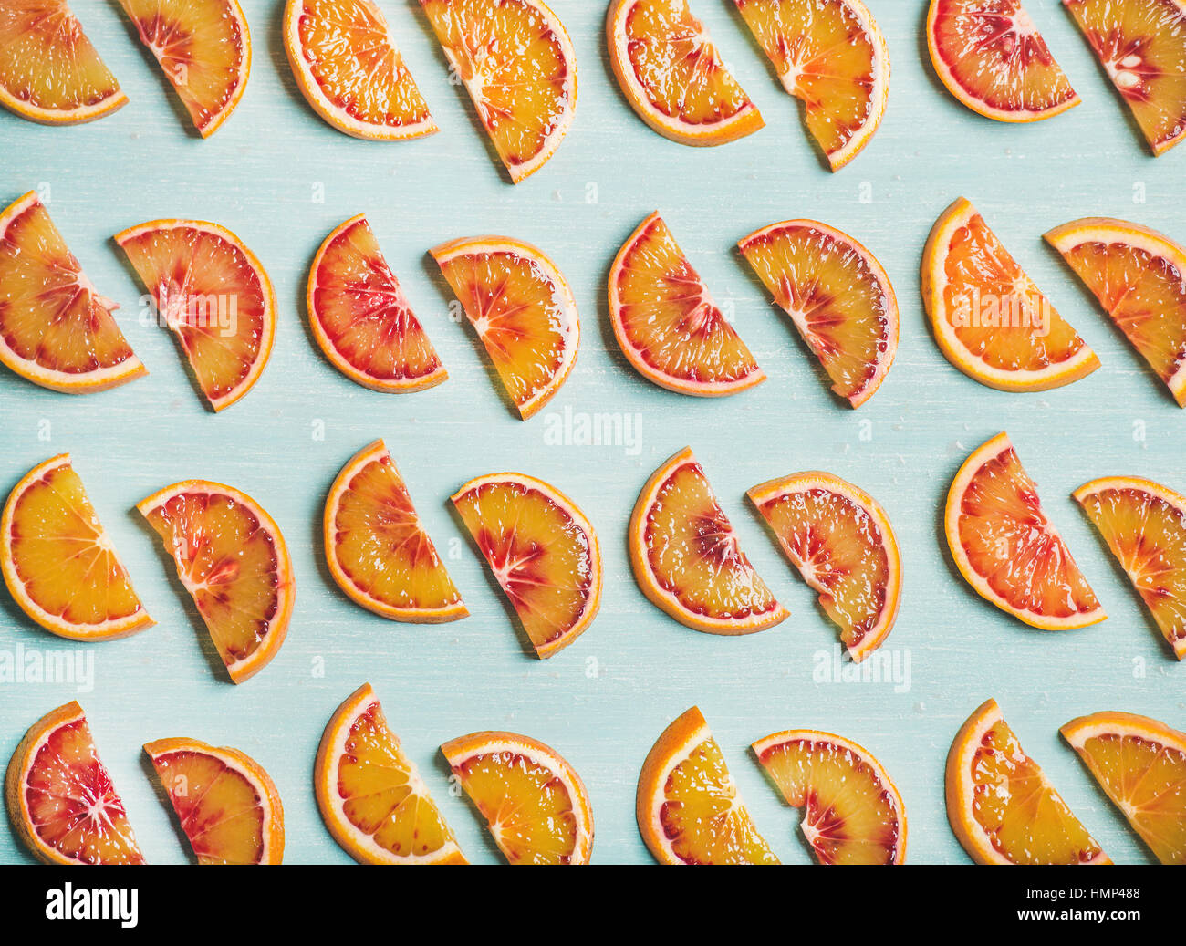 Fresh juicy blood orange slices over blue painted table background - Stock Image