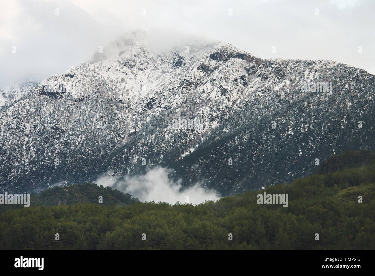Green slopes of the Taurus mountains covered with snow - Stock Image