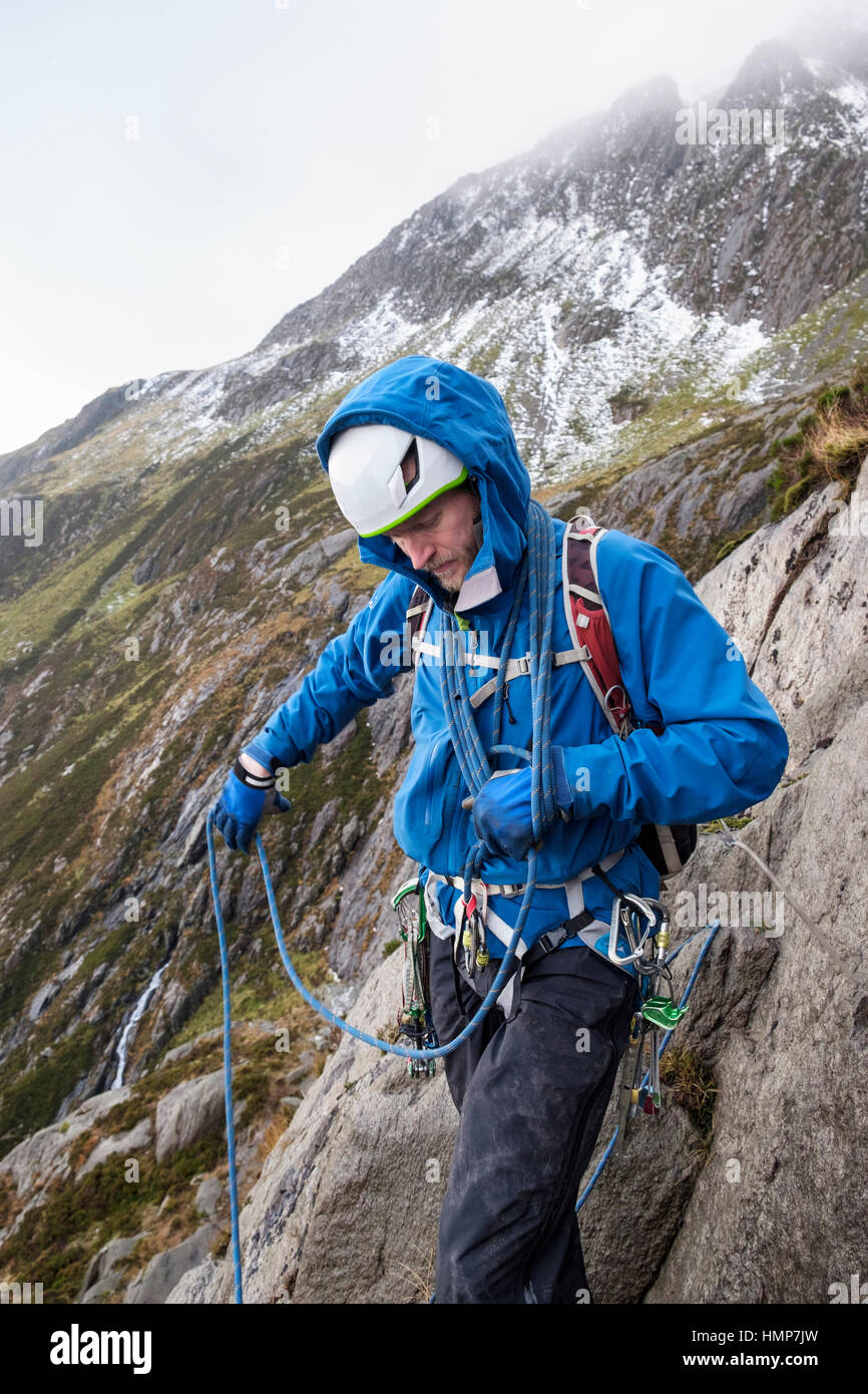 A rock climber coiling a climbing rope around his body preparing to lead a scramble in Cwm Idwal, Ogwen, Snowdonia, - Stock Image