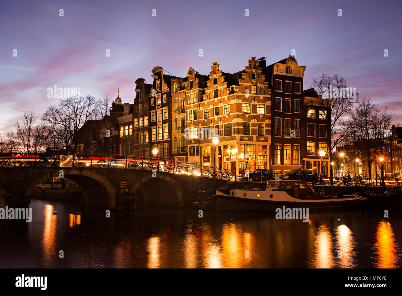 Amsterdam canal houses in traditional style next to a bridge over Prinsengracht en Brouwersgracht canals illuminated Stock Photo