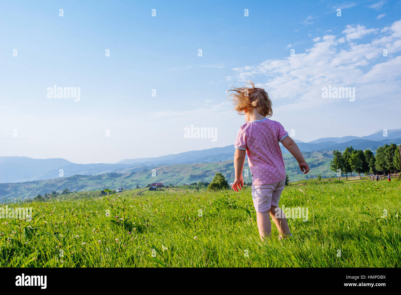 Little toddler girl running in a beautiful field - Stock Image