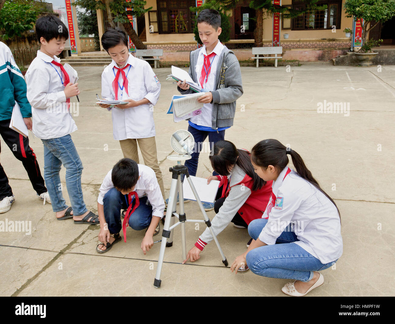 School children attending outdoor classroom, learning how to operate a sextant, Thai Giang Pho Boarding School. - Stock Image