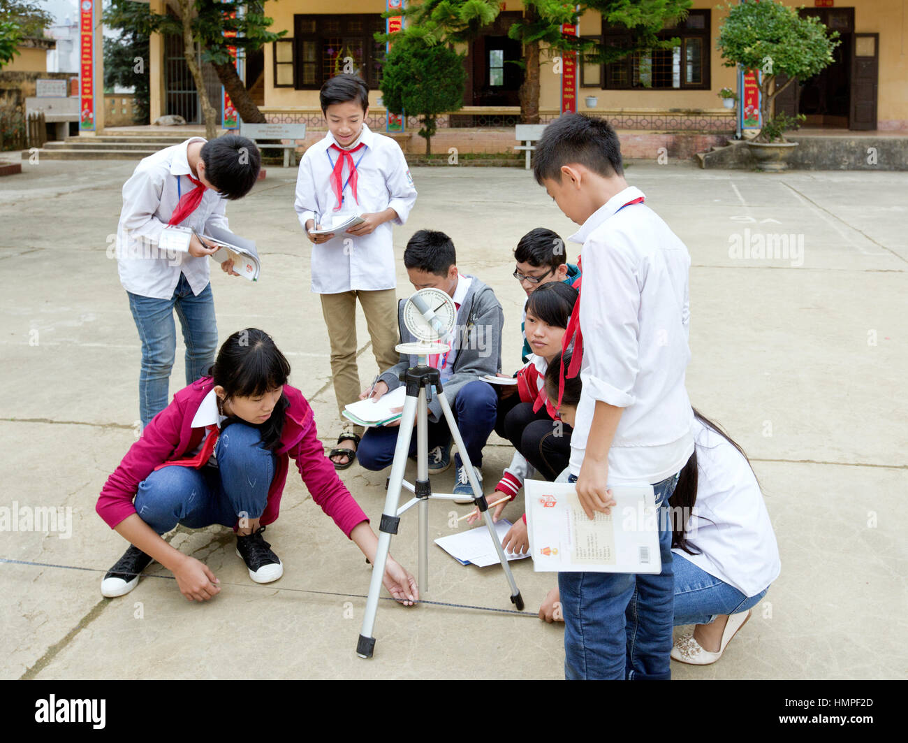 School children attending outdoor classroom, learning how to operate a sextant, Thai Giang Pho Bording School. - Stock Image