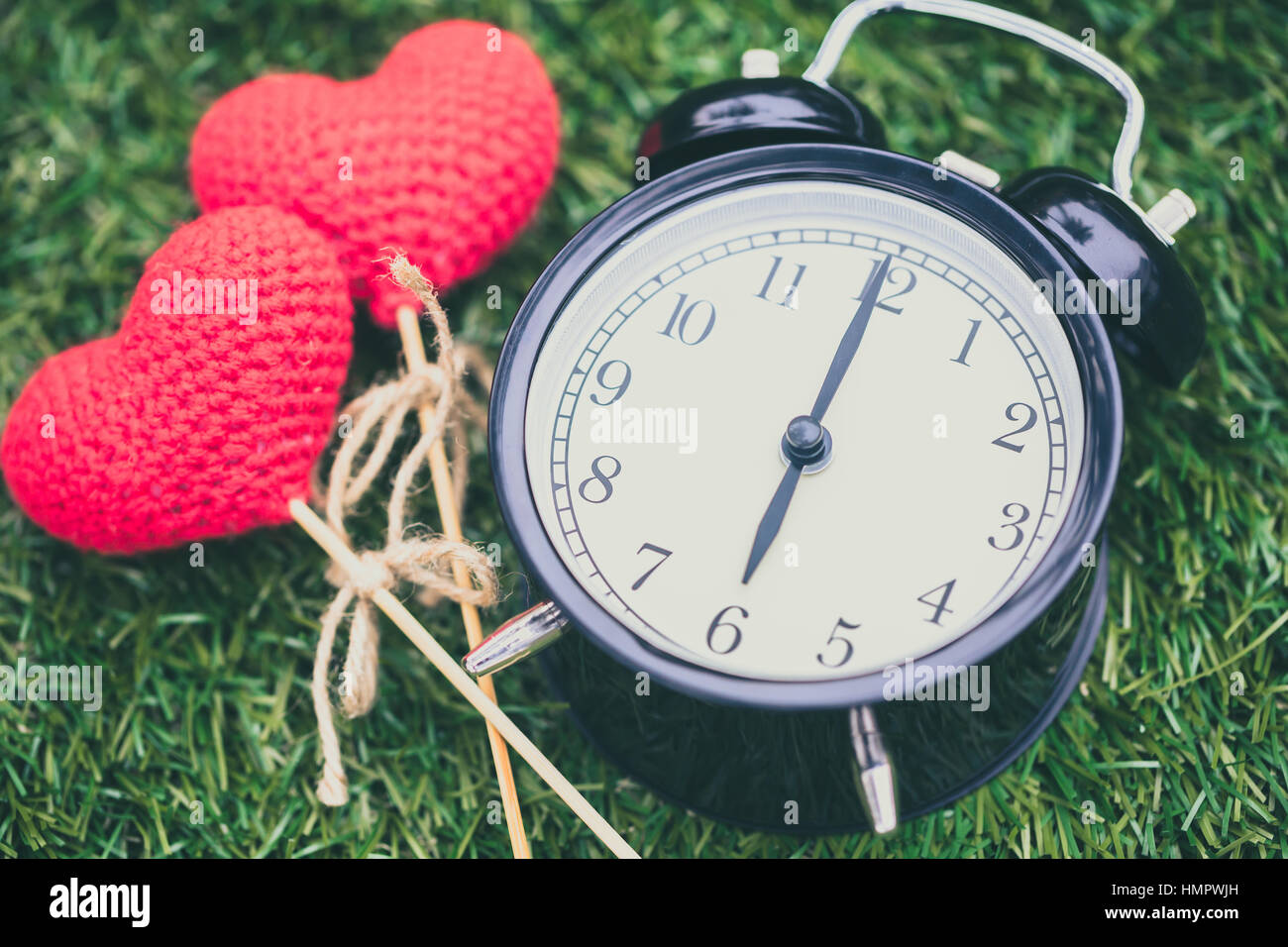 retro clock on grass time at 6 o'clock with red heart yarn