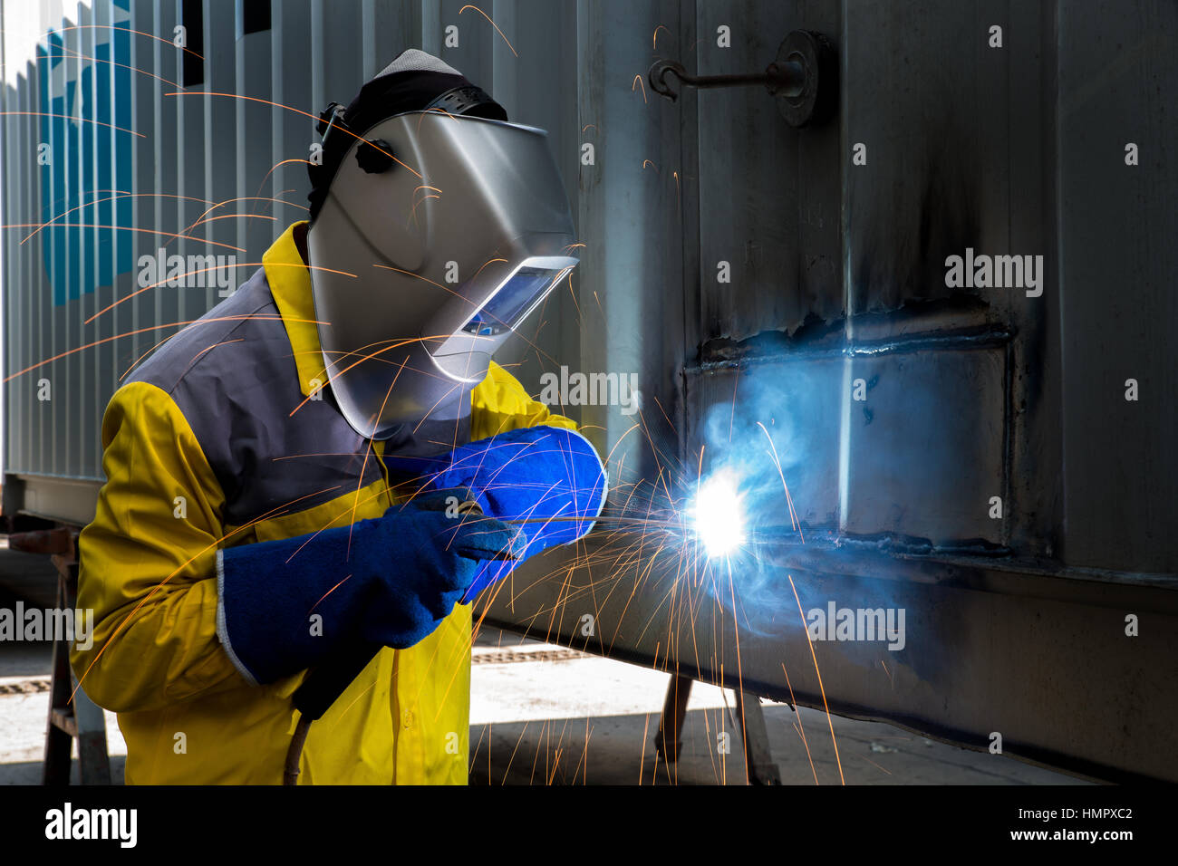Industry worker with welding steel to repair container structures manufacture workshop in factory industry. - Stock Image