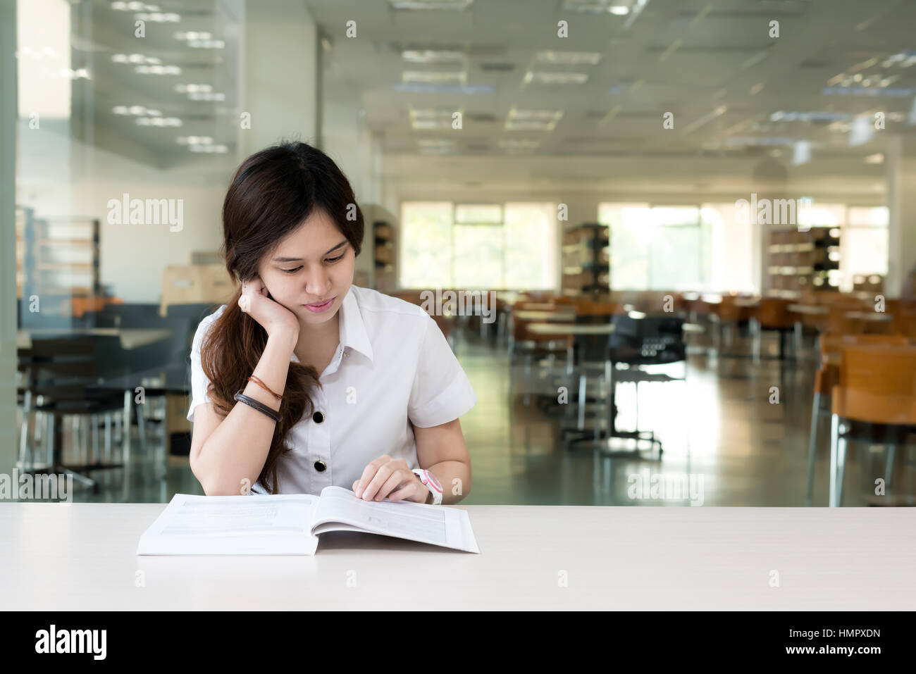 Asian student in uniform reading book in classroom at university. Stock Photo
