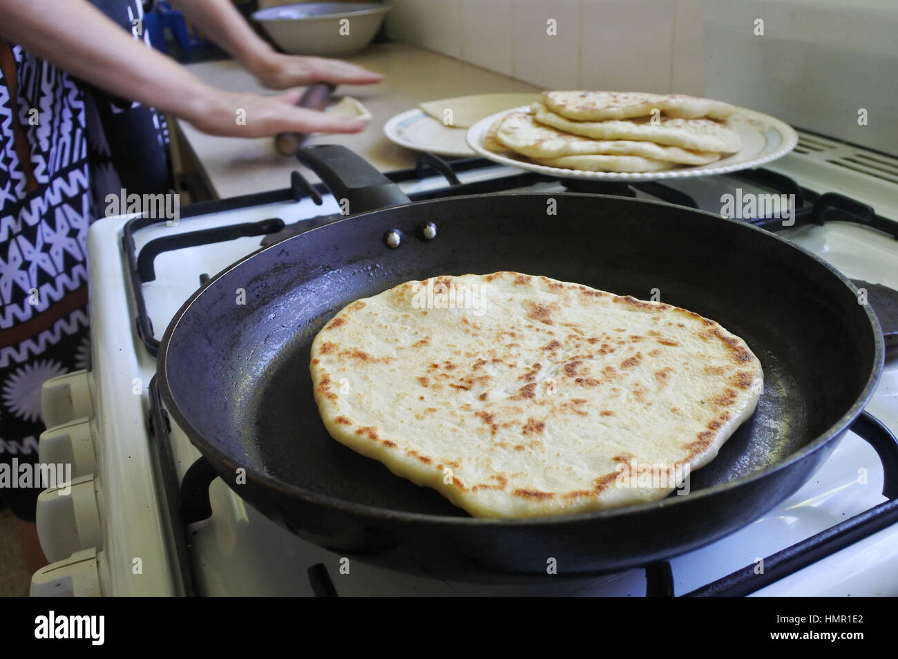 Indo fijian woman cooking homemade naan bread in the kitchen indian indo fijian woman cooking homemade naan bread in the kitchen indian food forumfinder Images