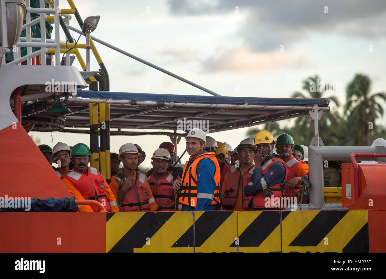 Oil workers in orange overalls are seen transfering from the